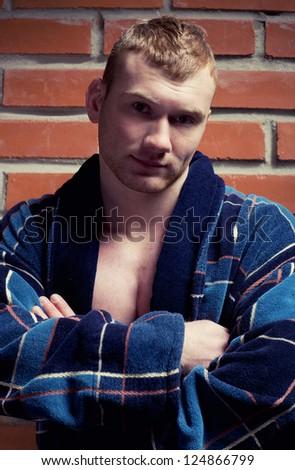 Young athlete man in bathrobe near brick wall - stock photo