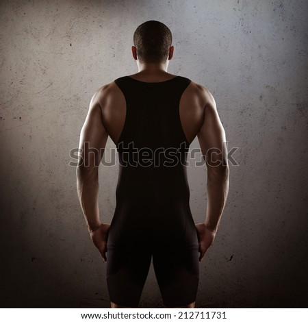 Young athlete on a dark concrete background