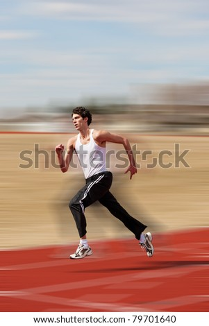 Young athlete running down the track with motion blur added. - stock photo