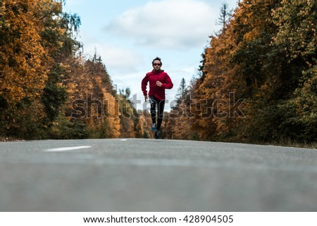 Young athlete running on the autumn road - stock photo