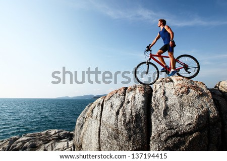 Young athlete standing on top of a mountain with bicycle and enjoying valley view - stock photo