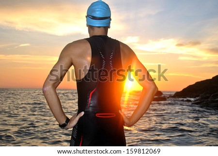 young athlete triathlon in front of a sunrise over the sea - stock photo