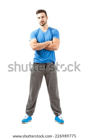 Young athlete with folded arms smiling looking at camera. Full body length isolated over white background. - stock photo