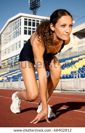 Young athlete woman at starting line - stock photo