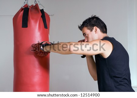 Young athlete working out by throwing punches at a heavy punching bag - stock photo