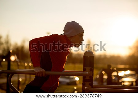 Young athlete working-out in an outdoor gym - stock photo
