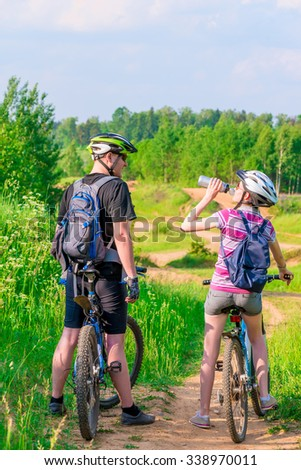 young athletes on bicycles rest and drink water - stock photo