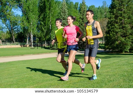 Young athletes running. Group of people jogging outdoors training for marathon. Happy caucasian healthy people exercising. - stock photo