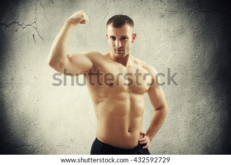 Young athletic bare-chested man in black pants is showing biceps on his right arm isolated on cracked concrete wall background