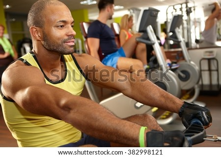 Young athletic black man training on rowing machine in gym. - stock photo