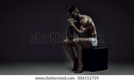 Young athletic brutal man like thinking statue