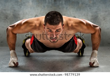 Young athletic fighter doing push ups in grunge environment./Push-up - stock photo
