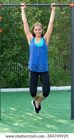Young athletic girl hanging on horizontal bar - stock photo