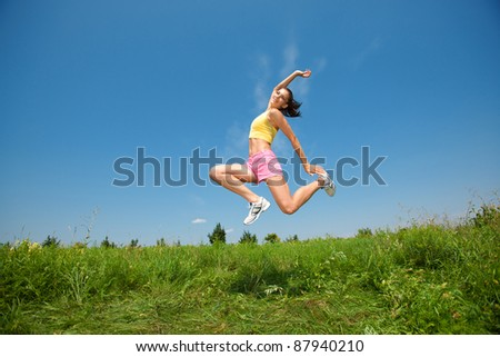young athletic girl jumping on grass - stock photo