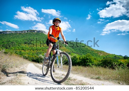 young athletic girl rides a bicycle on a mountain road - stock photo