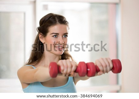 Young athletic girl with dumbbells in a gym - stock photo