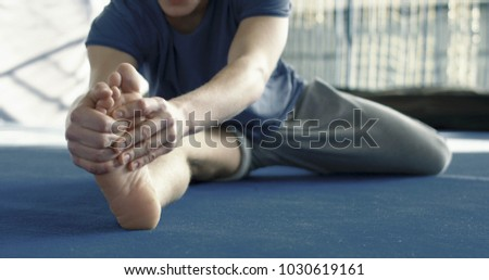 Young athletic man bending to leg while doing stretching exercises on floor in the gym in backlit.