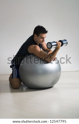 Young athletic man doing biceps curls on a balance ball. Isolated shot. - stock photo