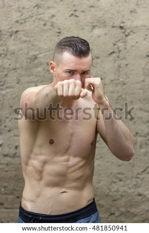 Young, athletic man doing boxing exercises / fighting / boxer