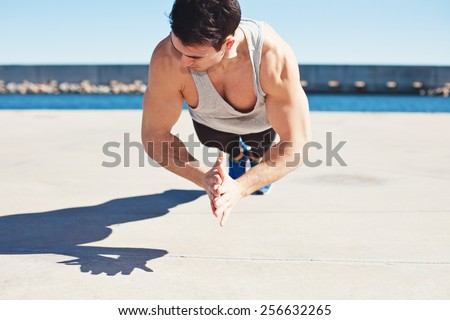 young athletic man doing sport exercise outdoors  - stock photo