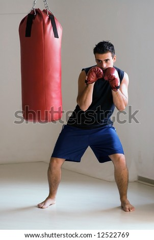 Young athletic man getting ready to unleash a punch on a heavy punching bag - stock photo