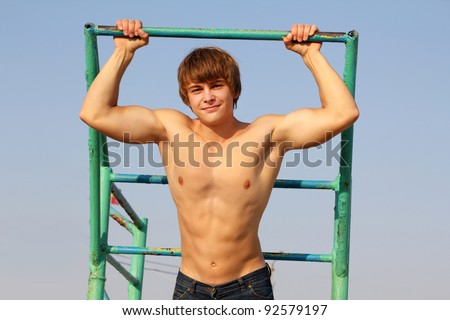 Young athletic man  holding on to horizontal bar, outdoors