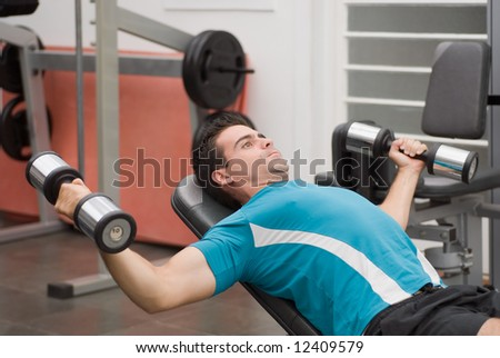 Young, athletic man in the gym doing a chest press on a weight bench - stock photo