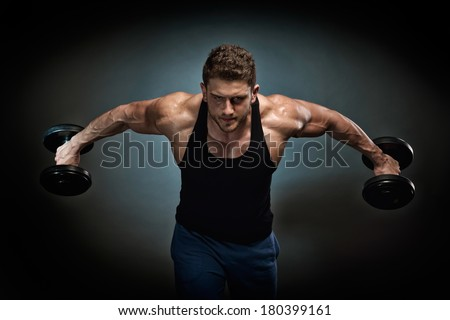 young athletic man lifting weights - stock photo