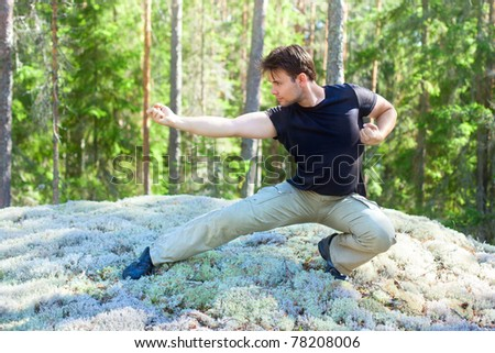 Young athletic man martial art training outdoors. - stock photo