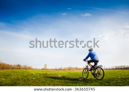 young athletic man on a bicycle rides on the green meadow road