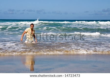 young athletic man posing on the sea shore on blue day
