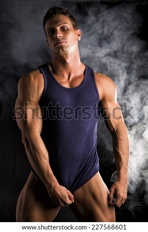 Young athletic man pulling down tanktop on ripped muscular torso, on dark smoky background - stock photo