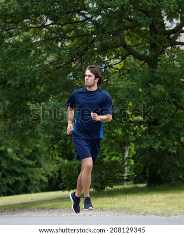 Young athletic man running outdoors in park - stock photo