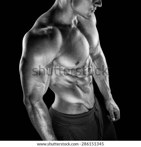 Young athletic man torso showing six pack abs. Handsome power athletic young man with great physique. Black and white photo - stock photo