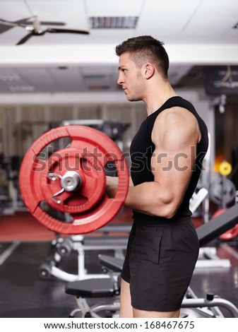 Young athletic man working his biceps with heavy barbell at the gym - stock photo