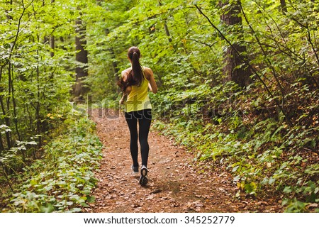 Young athletic sporty girl with long hair in green sleeveless shirt training in green forest during summer autumn season with lots of leaves fallen on forest path. Back view with copy space - stock photo