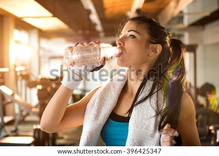 Young athletic woman drinking water gym stock photo 396425347 young athletic woman drinking water in gym sciox Choice Image