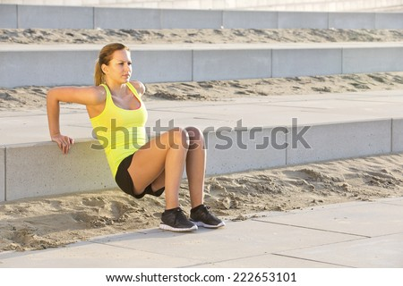 Young, athletic woman excercising her upper body during a bootcamp training session on a beach boulevard - stock photo