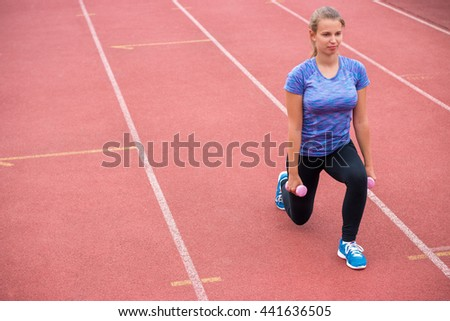 Young athletic woman exercising with dumbbells outdoors
