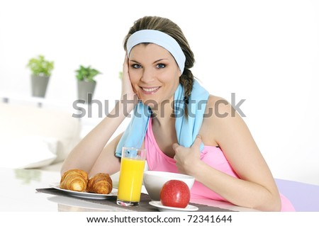 young athletic woman having breakfast - stock photo