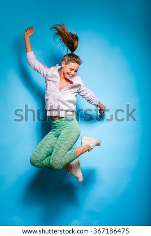 young athletic woman in fitness equipment jumping on blue background - stock photo