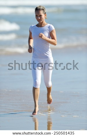 young athletic woman jogging on the beach in summer sunny day - stock photo