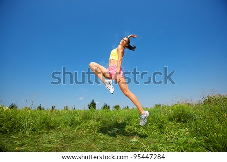 young athletic woman jumping on grass - stock photo