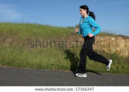 Young athletic woman running on a trail - stock photo