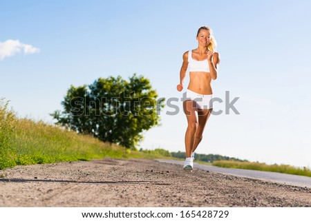 young athletic woman running on the road, exercise outdoors - stock photo