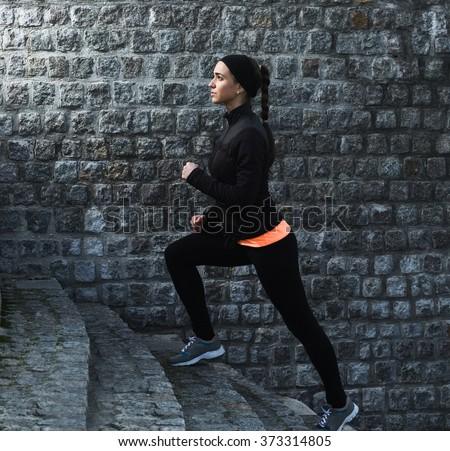 Young athletic woman running up the stairs near brick wall - stock photo