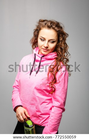 Young athletic woman standing against gray background. Fitness club concept image with copy space