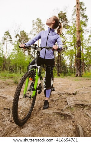 Young athletic woman with bicycle in forest