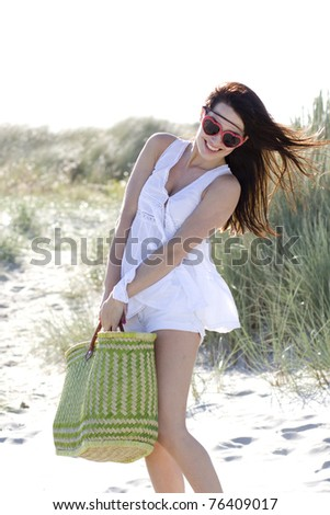 young atractive woman is holding green  bag on beatch - stock photo