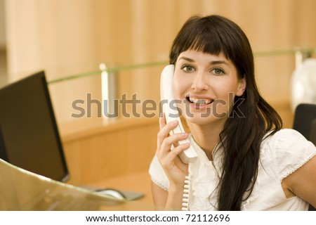 young atractive woman receptionist with phone talking to customers - stock photo